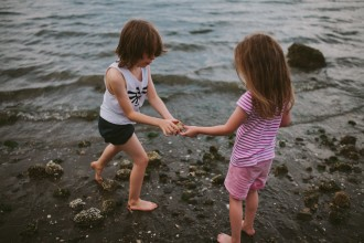 boy and girl exploring on the beach by Meghann Prouse