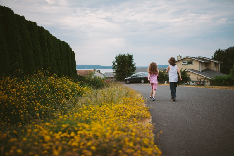 boy and girl walking down a street lined with yellow flowers by Meghann Prouse