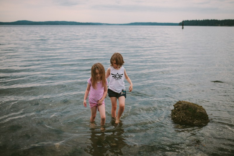 boy and girl walking in the water by Meghann Prouse