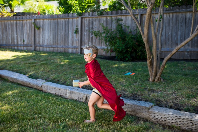 boy in a red cape running in the yard by Nicole Cross