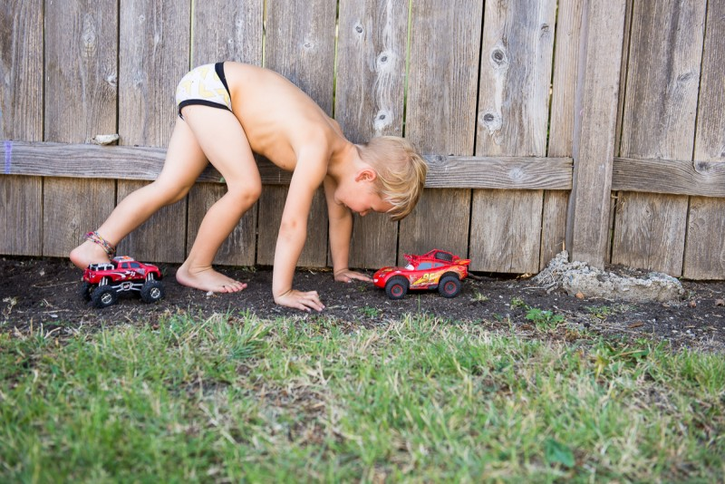 boy playing in the dirt with his cars by Nicole Cross