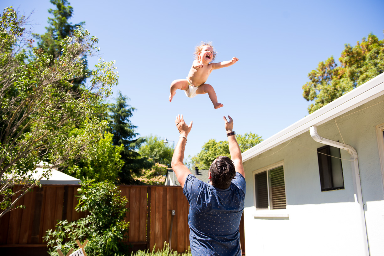 dad throwing daughter up in the air by Nicole Cross