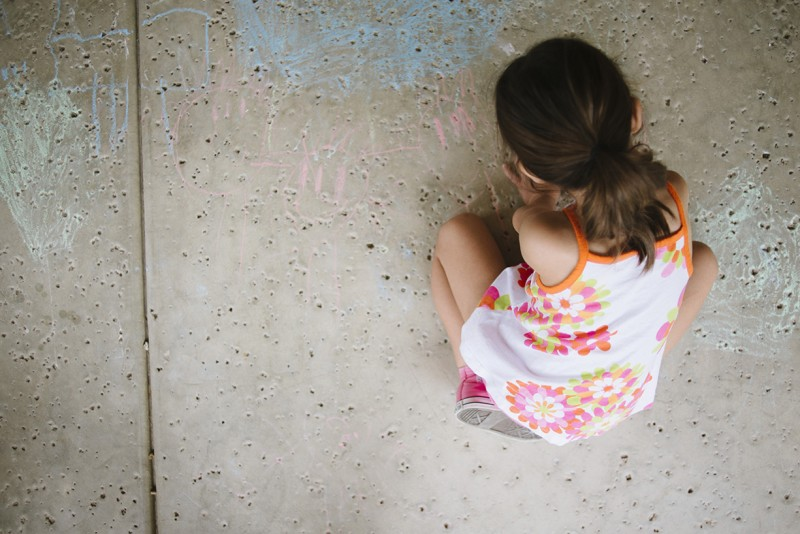 girl drawing on sidewalk with chalk by Pamela Bernasconi
