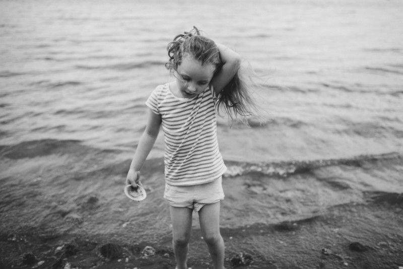girl holding her hair back while in the water by Meghann Prouse