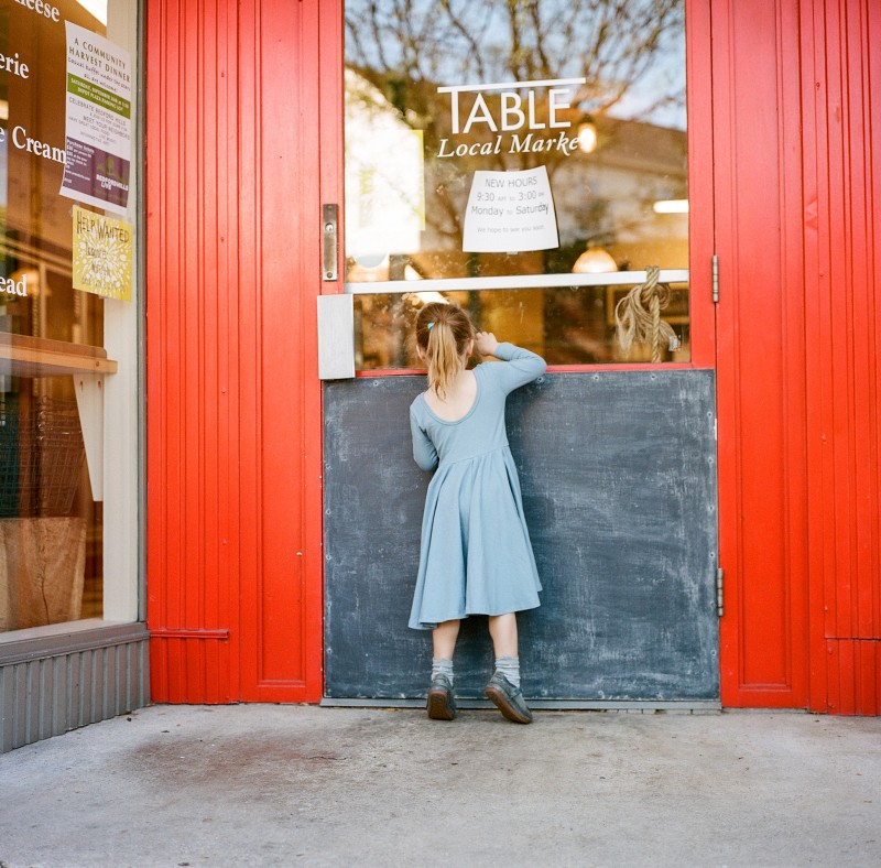 girl peeking through a store window by Elena Wolfe