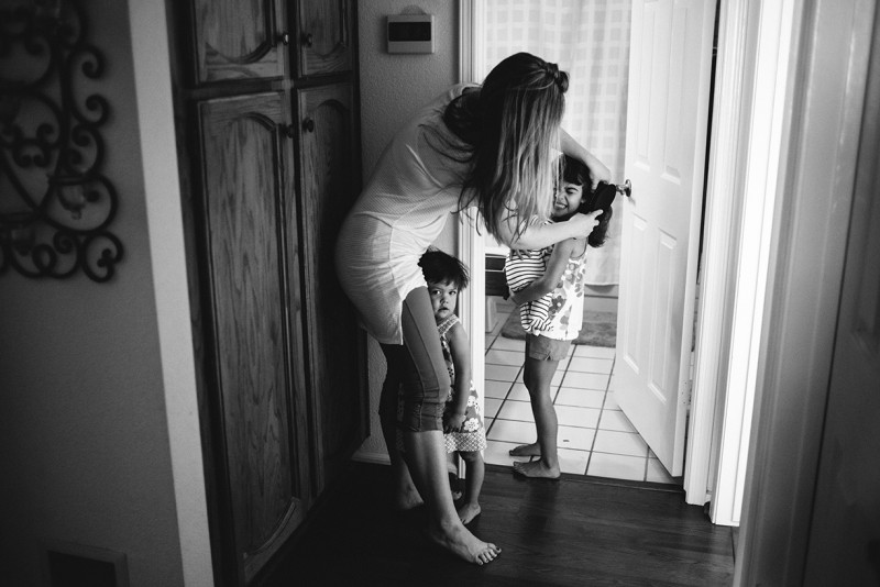 mom brushing daughters hair by Pamela Bernasconi