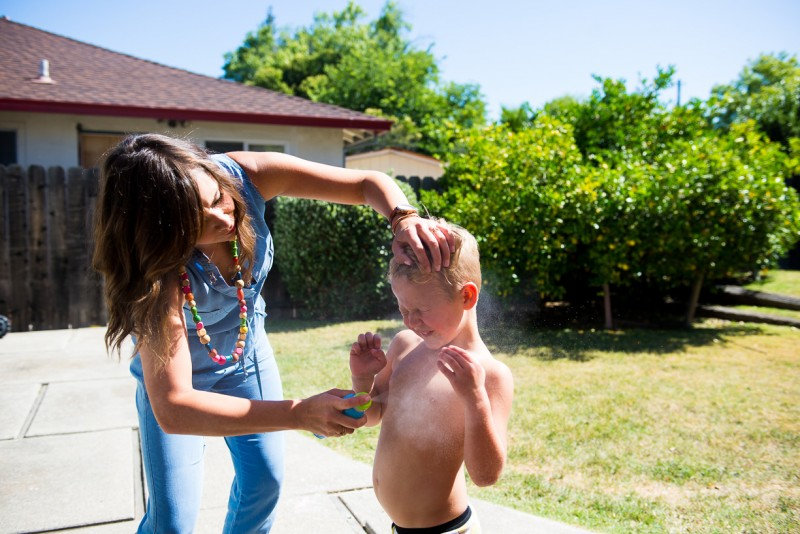 mom spraying son with sunscreen by Nicole Cross