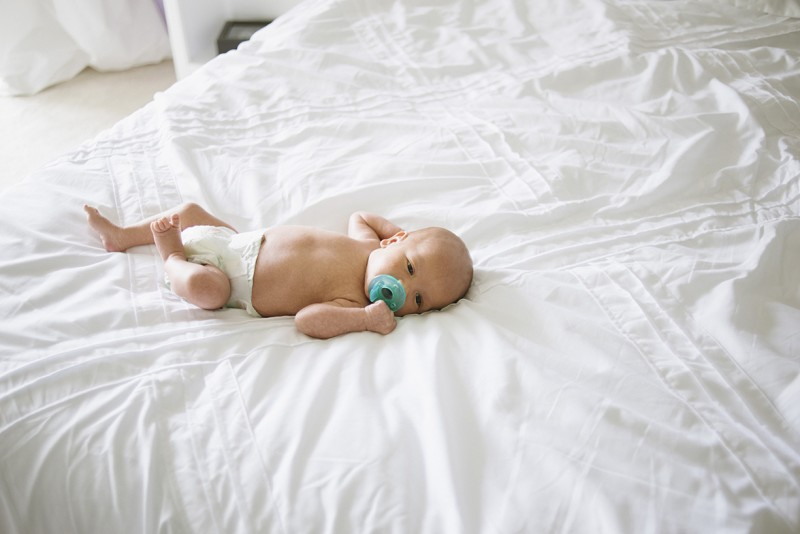 small baby laying on bed by Pamela Bernasconi