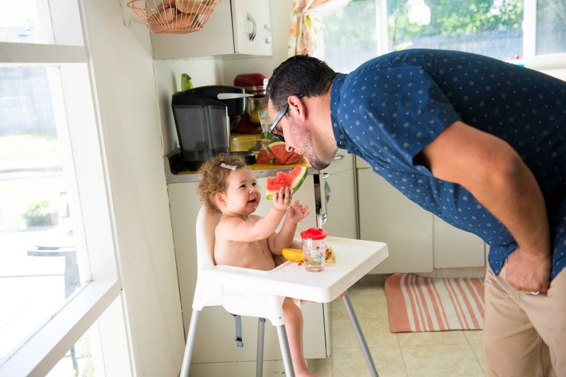 toddler feeding dad watermelon by Nicole Cross