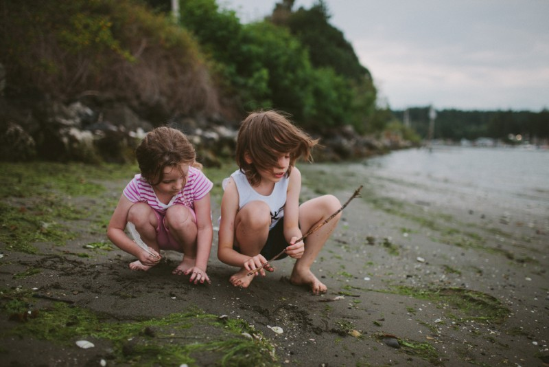 two friends playing with a stick on the beach by Meghann Prouse