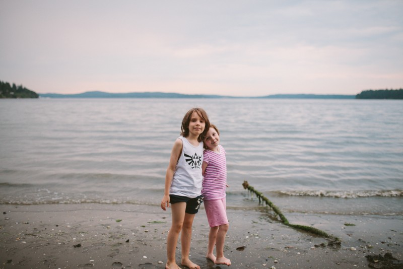two friends standing on the beach by Meghann Prouse
