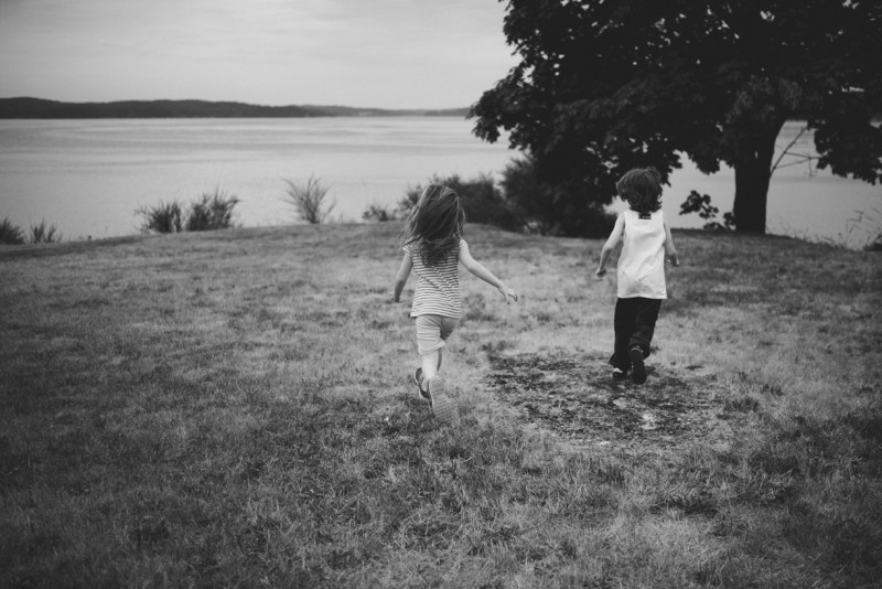 two kids running in the grass by Meghann Prouse