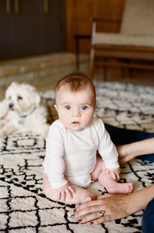film picture of baby sitting on a black and white rug by Angie Mertz
