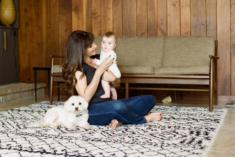 picture of mom sitting by dog and holding child in a retro room by Angie Mertz
