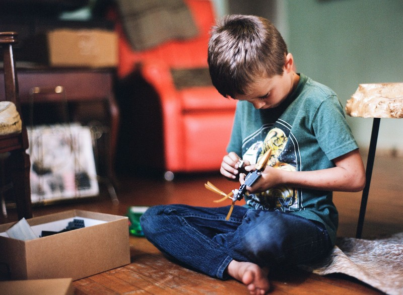 boy playing with legos by Bernadette Madden