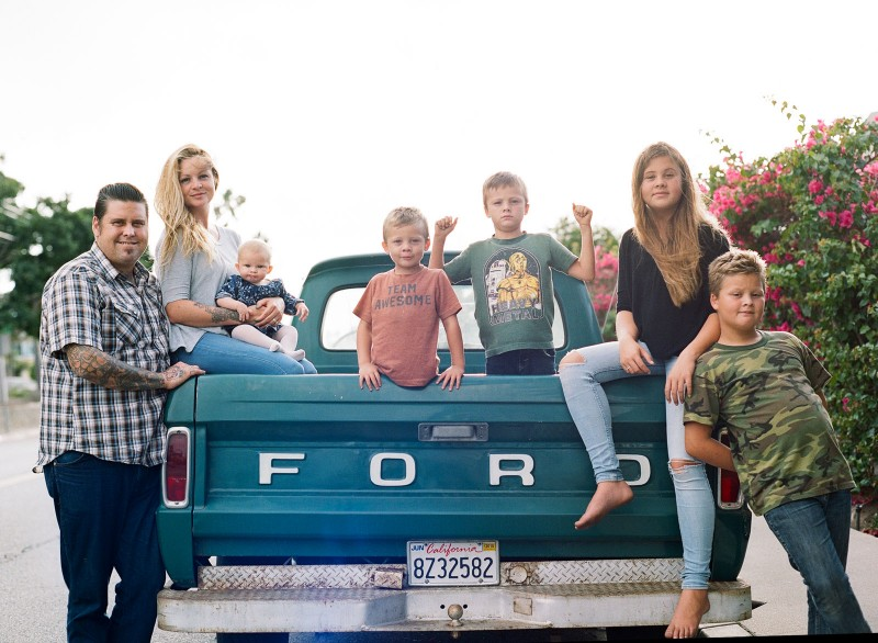 family sitting in their vintage Ford truck by Bernadette Madden
