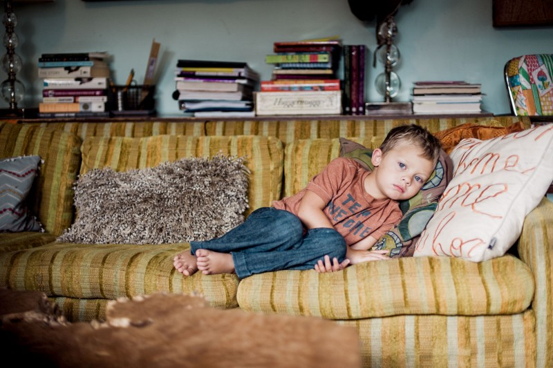 picture of boy laying on a yellow vintage couch by Bernadette Madden