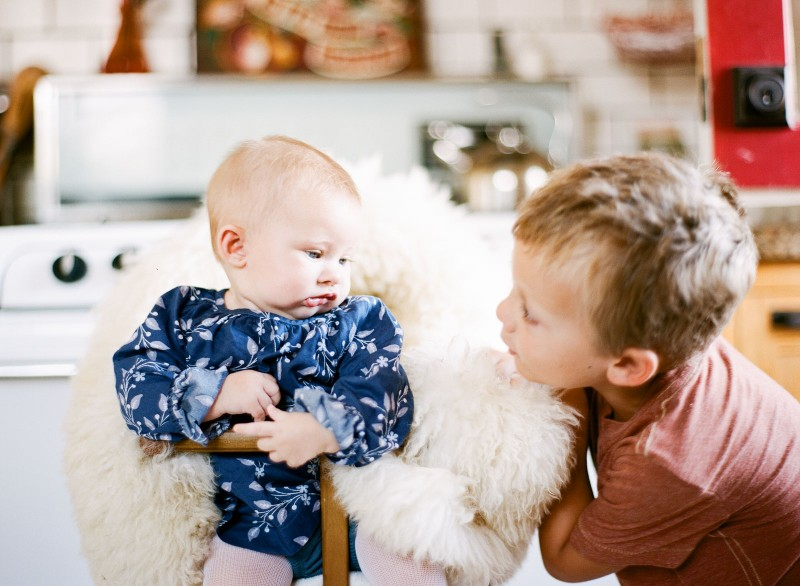 picture of brother looking at baby sister by Bernadette Madden