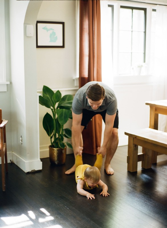 dad playing with daughter in yellow outfit by Paige Gabert