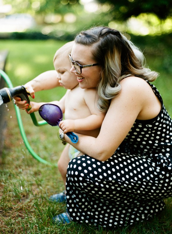 mom helping kid water garden with a hose by Paige Gabert