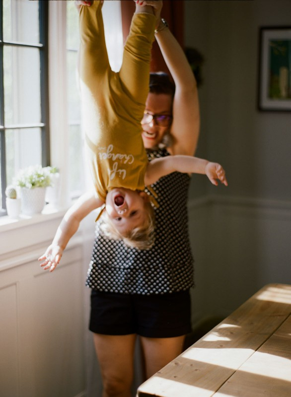 mom holding daughter upside down by Paige Gabert