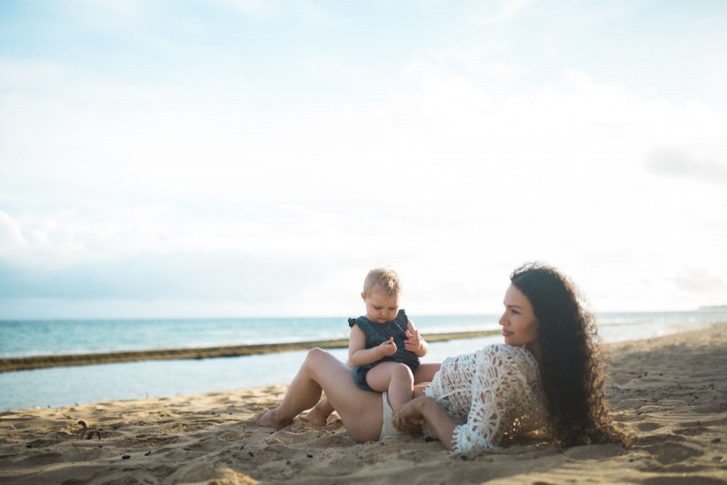 photo of woman and baby laying on the Hawaii beach by Cadence Feeley