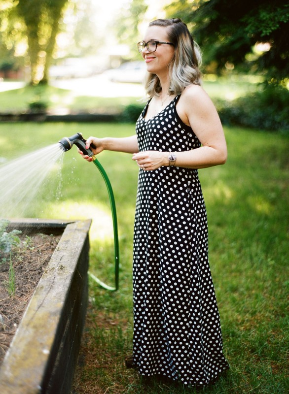 photo of woman watering the garden by Paige Gabert